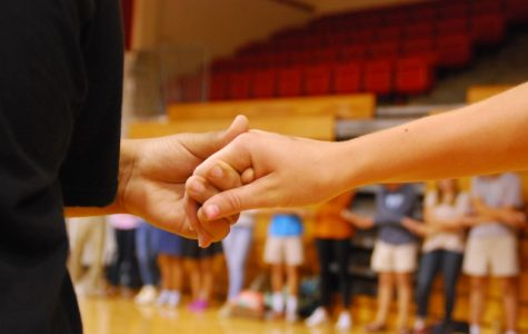 FHS students cross their hands in prayer at a recent Fellowship of Christian Athletes meeting.