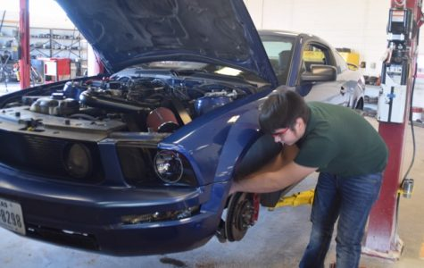 Ernesto Neri, a member of the Auto-Tech class, replaces his suspension in his own blue Mustang.