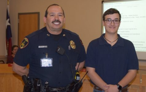 Officer Chris Ayala commends sophomore Dane Moellendorf at the school board meeting on Feb. 13 for his advancement to the state competition.
