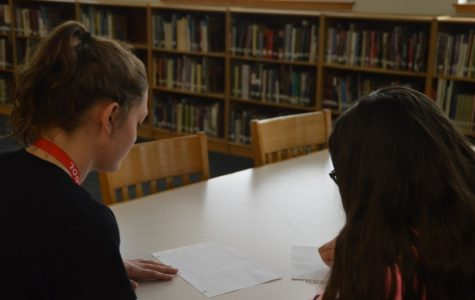 A FHS student slyly slides her paper over to a fellow classmate to show the art of cheating in progress.
