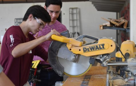 Roberto Romero and Daniel Sanz work to cut lumber for this year's Tiny House project.