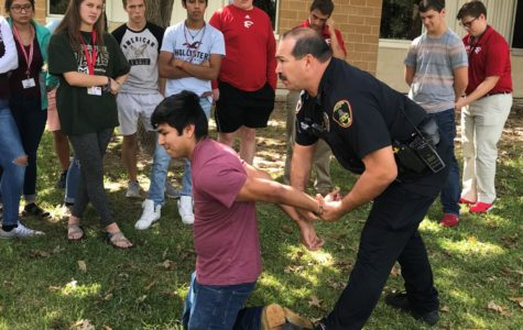 Officer Ayala demonstrates the proper technique for placing handcuffs on student volunteer, JoseLuis Andrade.