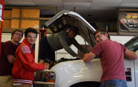 Kyle Ritter, Gary Sorola, Calvin Todd and Connor Kennedy work on a car in their Auto Tech class.