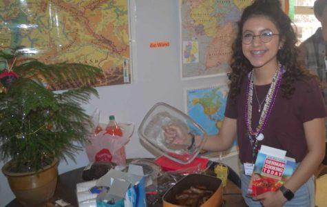 Yatzari Galindo enjoys the bratwurst during the German Club party celebrating Mardi Gras.