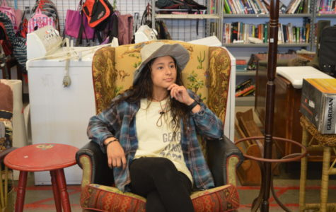Christina Arzapala ponders over whether she should purchase the chair she finds so comfortable at Goodwill.