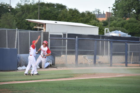 Coach Dietrich signals TJ Tomlinson to round third for the first score of the game.