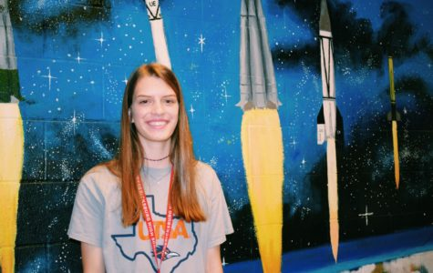 Sophomore Carlotta Wilkinson, one of the few girls in engineering, poses in front of rockets to support women in STEM.