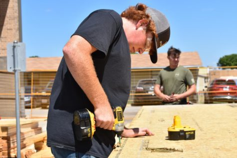 Junior Jacob Land drills a screw into the plywood of the Casa Uber Alles house as they began construction this school year.
