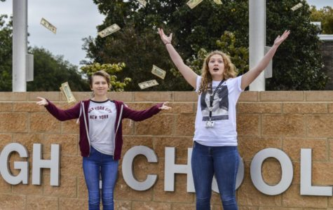From left to right, Valerie West and Lauren Guzy throw up money in front of the school