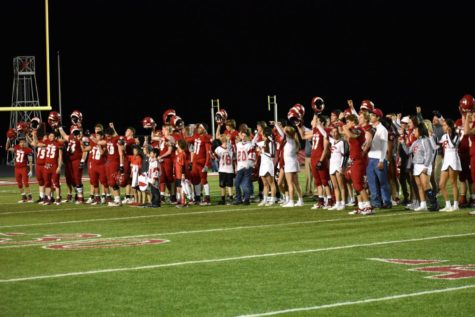 Billie football players, cheerleaders, and coaches sing the Alma Mater at the last home game.