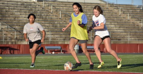 Senior Julia Freeborn attacks the goal during a drill in attempt to score. Sophomore Sadie Eidson and Jinior Ana Iglesies Chirinos follow close behind close behind trying to defend their goal.