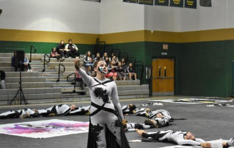Katie Robertson with other color guard members behind her performing at competition.