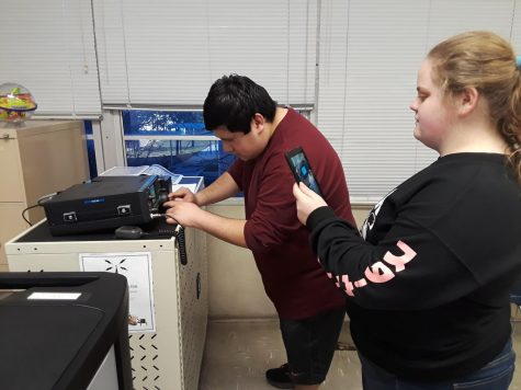 Members of the newly formed radio club work with the equipment to be able to communicate with others.
